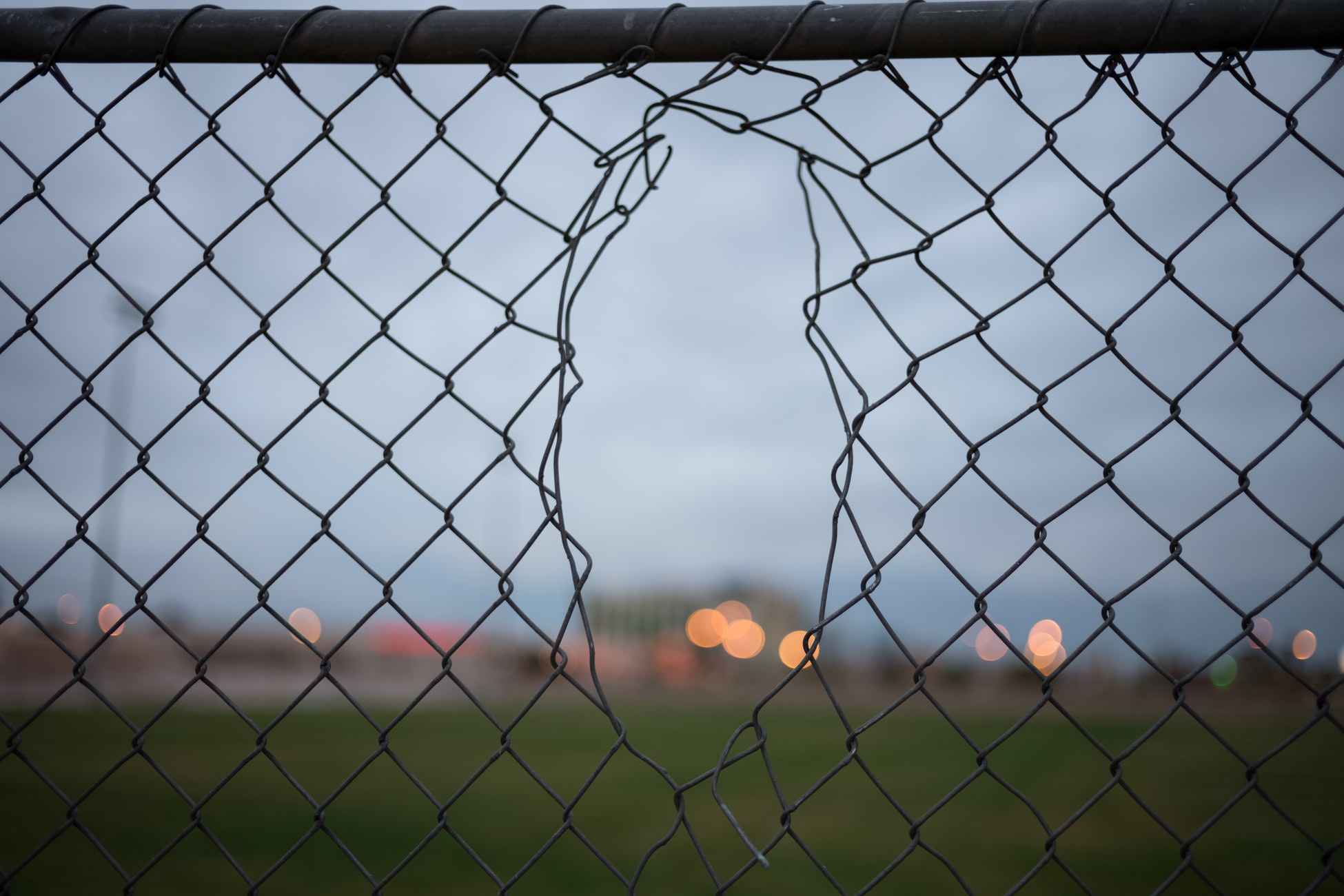 A broken chain link fence creates security vulnerabilities