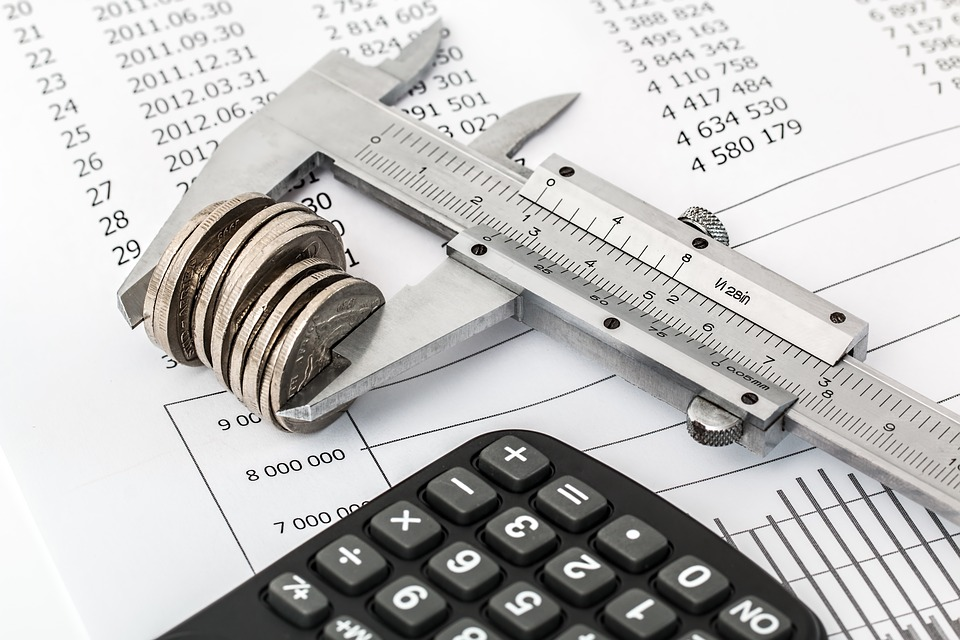 A stack of coins in a measuring device next to budget papers and a calculator